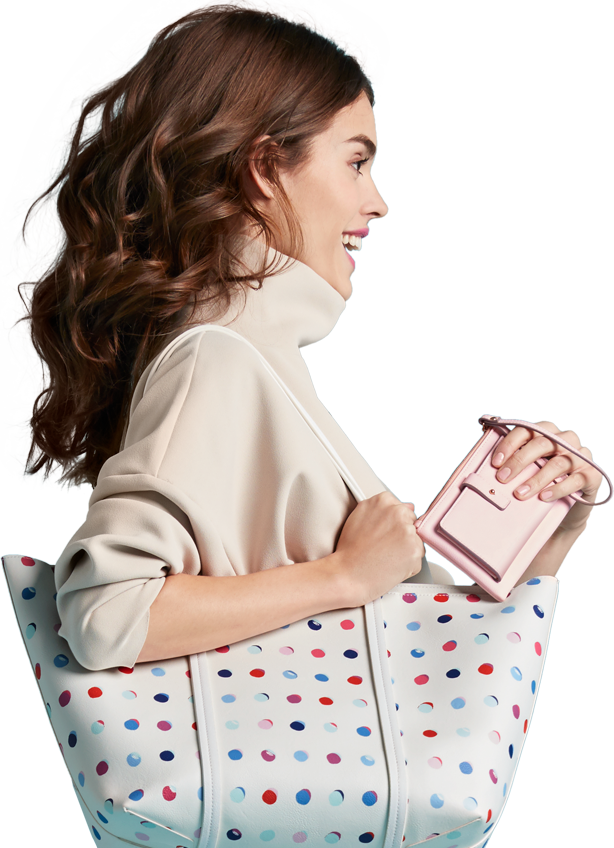 Woman smiling and jumping with a polkadot tote