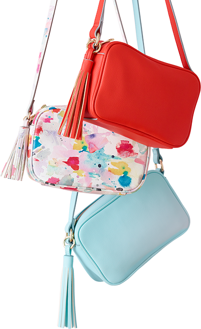 A red, a floral, and a blue purse with tassels hanging.