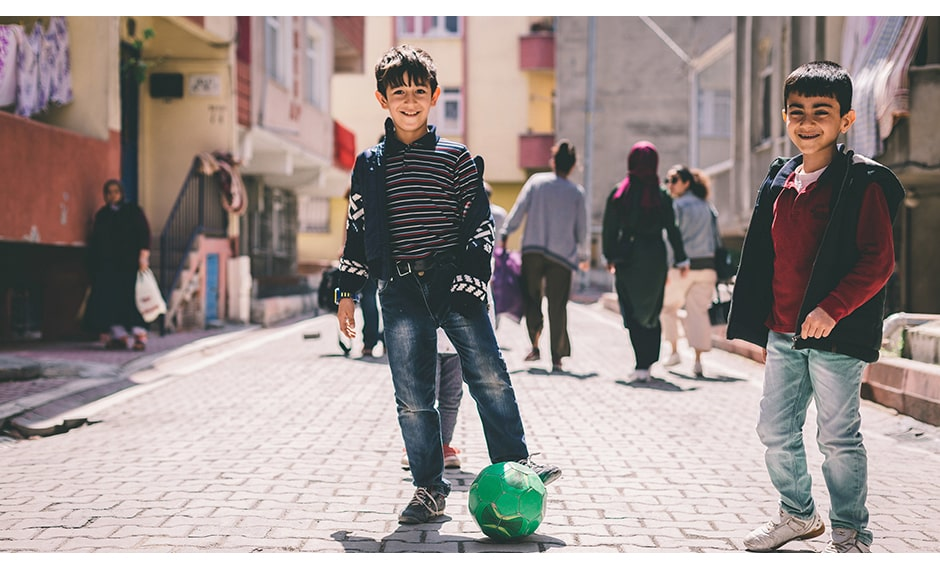 Two boys smiling with a soccer ball.