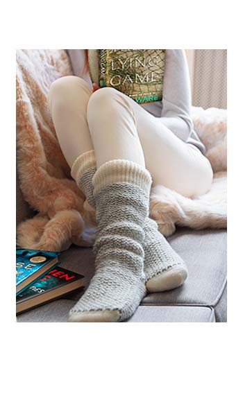 Person curled up on a couch wearing reading socks and reading a book