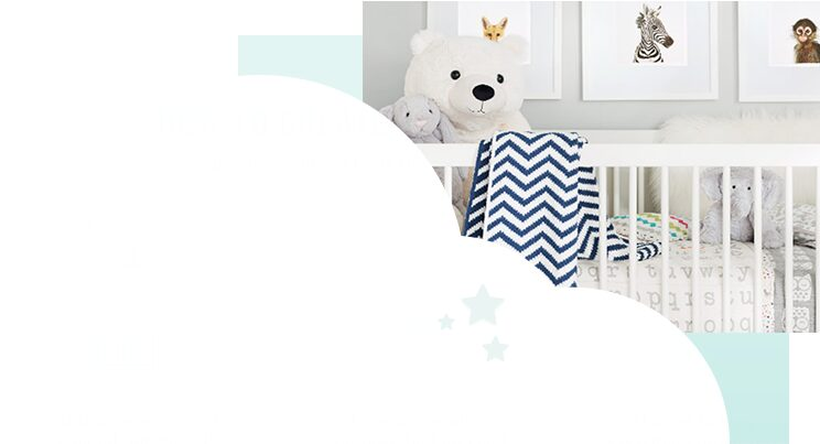 White crib filled with soft baby toys, baby bedding and blankets in front of framed nursery wall art