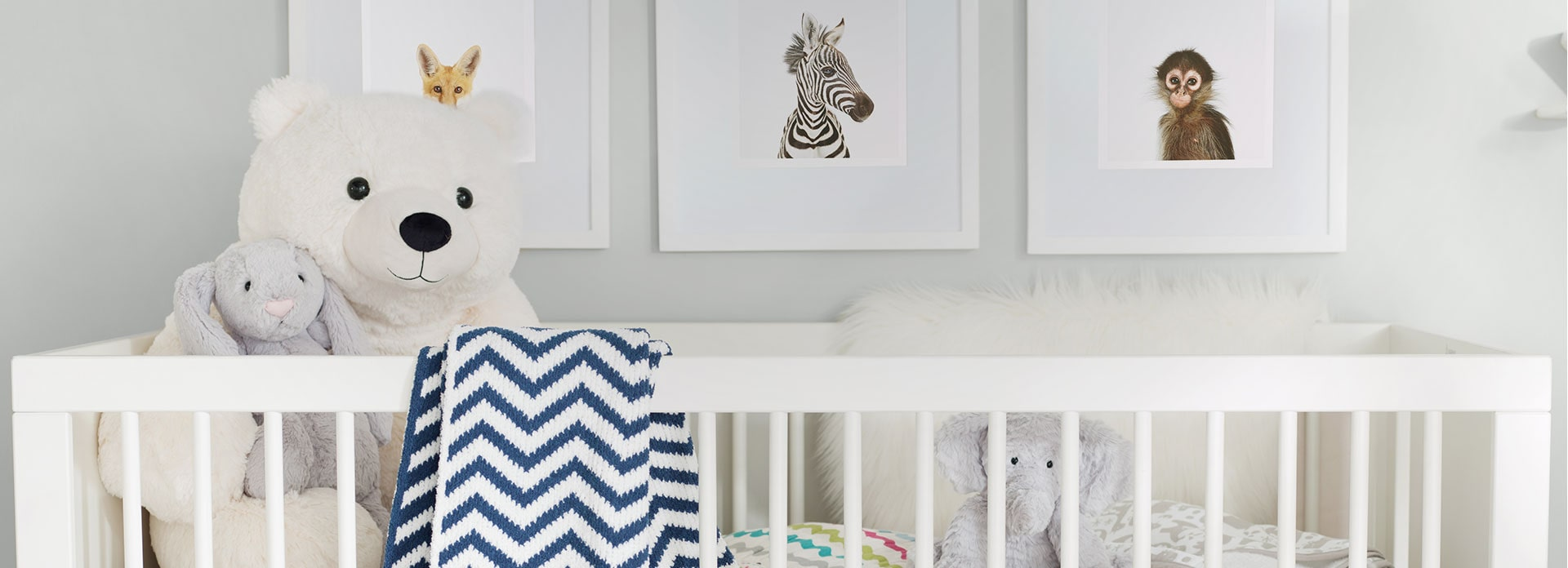 White baby crib with a bear and bunny plush inside and a chevron blanket draped over it.