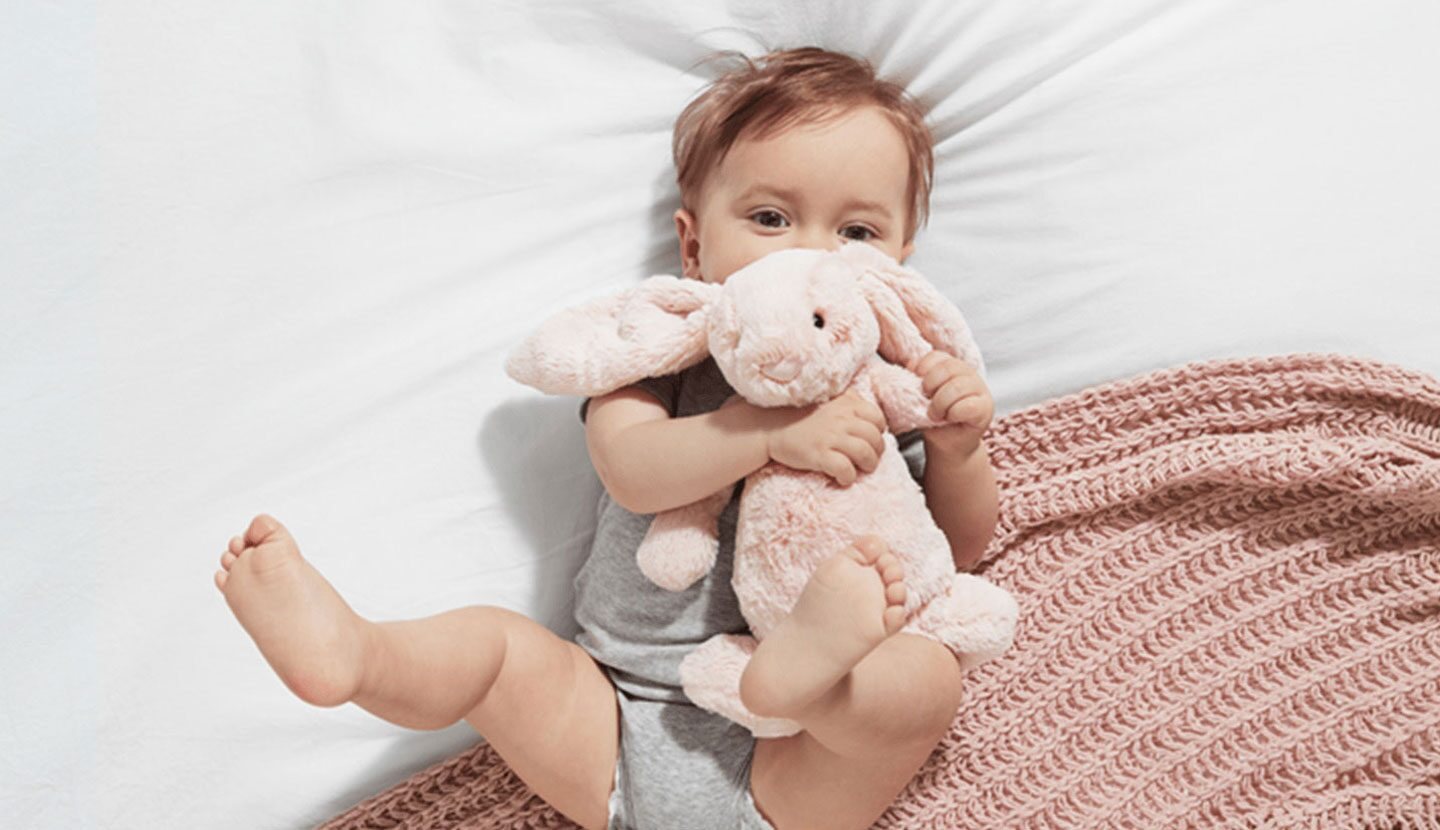 Baby laying on its back wearing a grey onesie holding a pink bunny stuffed animal.