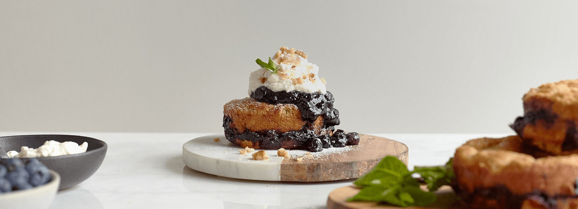 French toast cake drizzled with blueberry sauce and whipped cream on top of a wooden and marble platter.