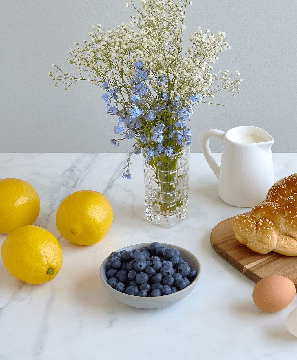 A bouquet of blue flowers and baby's breath in a glass vase with lemons, blueberries and a loaf of bread on a white table.