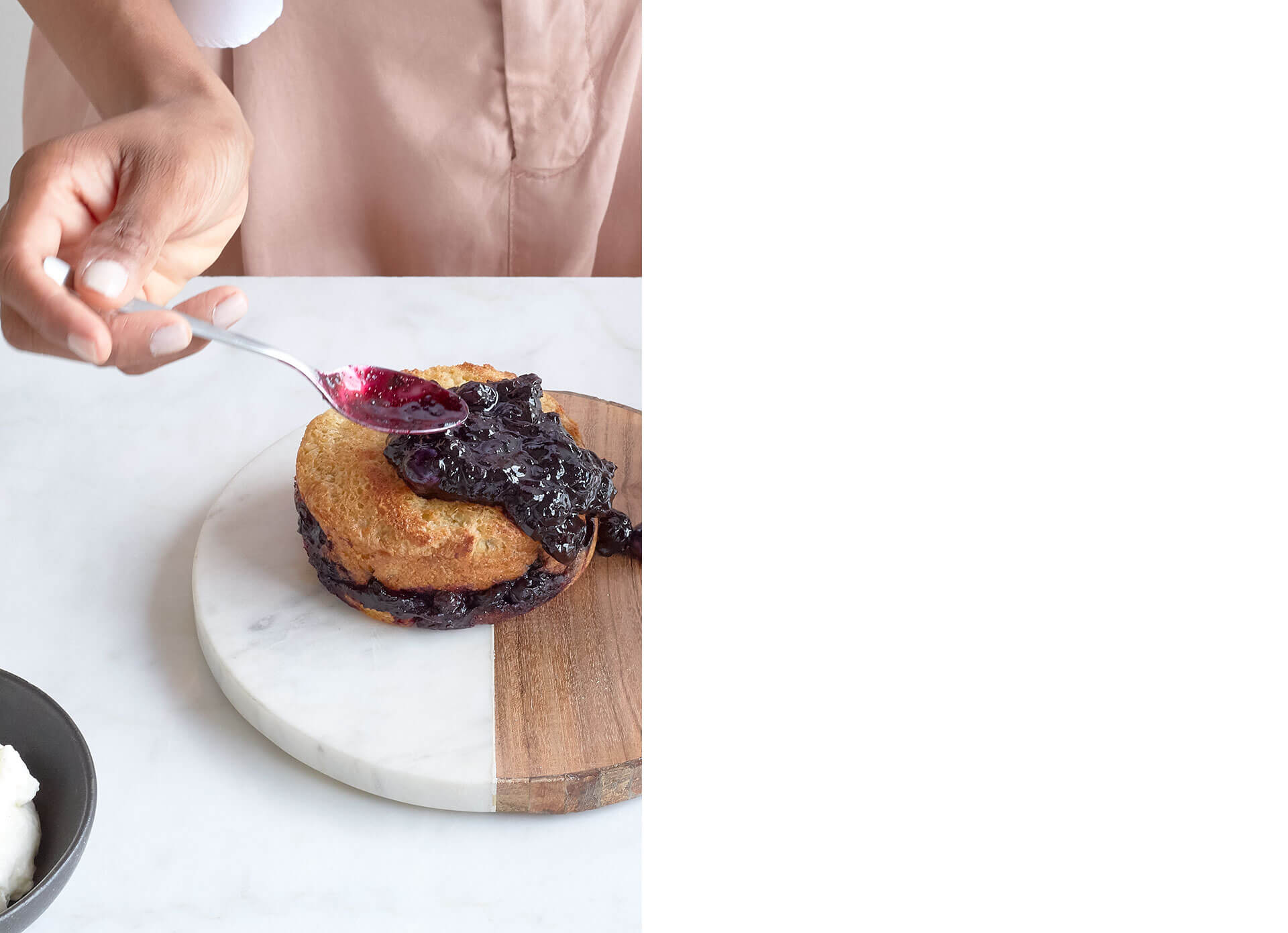 Woman spreads blueberry sauce with a spoon over french toast cake.