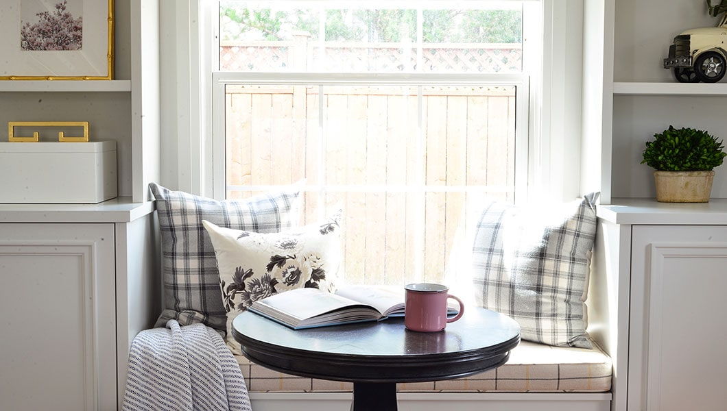 Scene depicting a bay window with light pouring in, pillows, an open book and coffee mug surrounded by built in shelves.