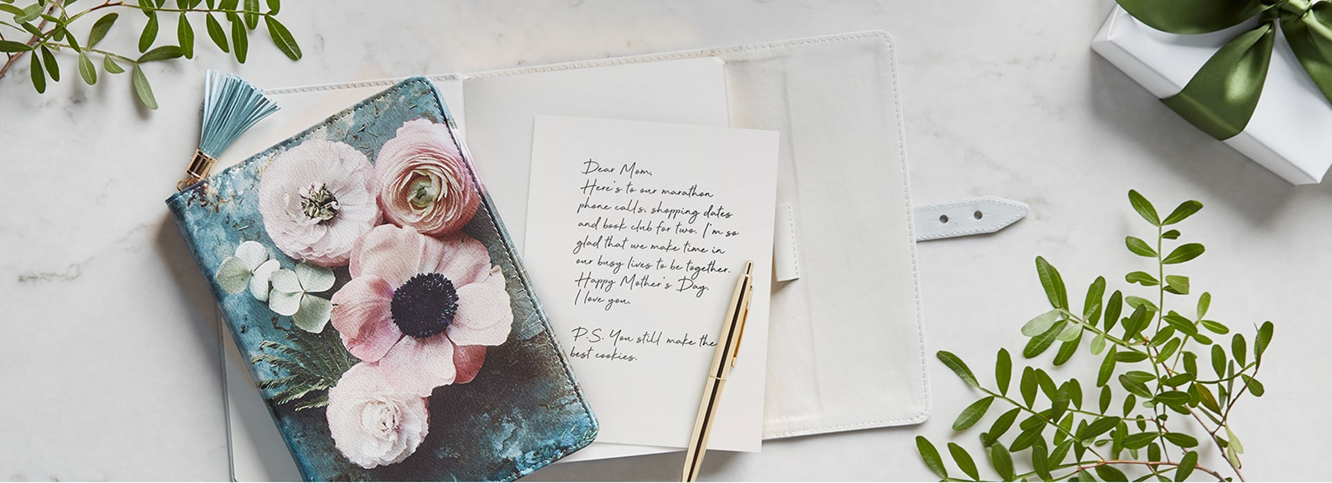 A journal with a letter written in it lies open on a table and a floral journal is on top with a pen next to it.