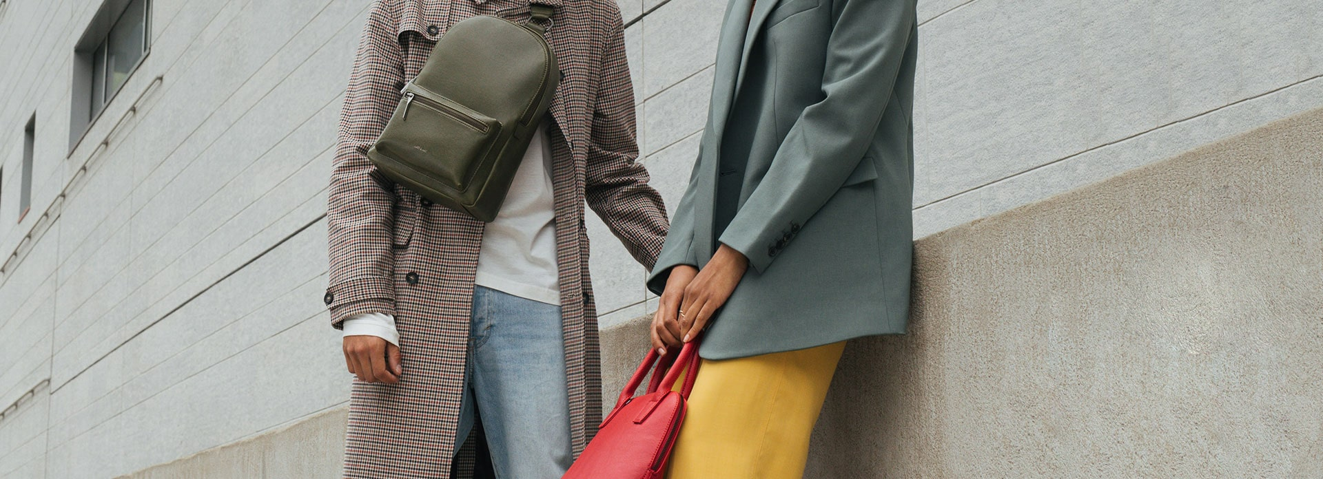 Man in a trench coat with a backpack across his body casually standing next to a woman holding a red purse in her hands.