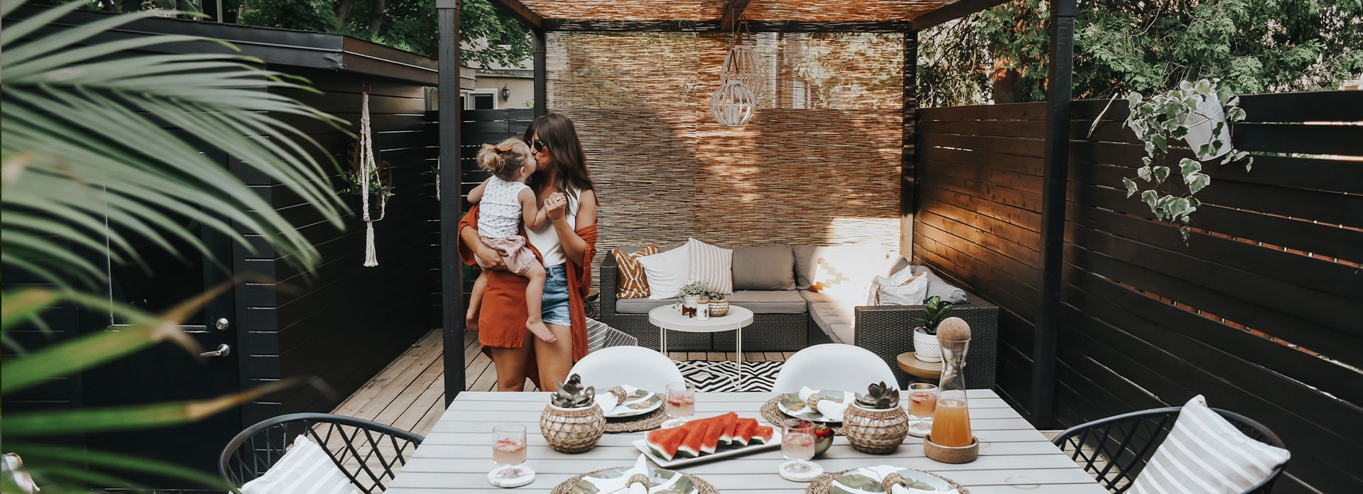Blogger DanetaB kissing her daughter in her backyard oasis with a summer table set in the foreground.