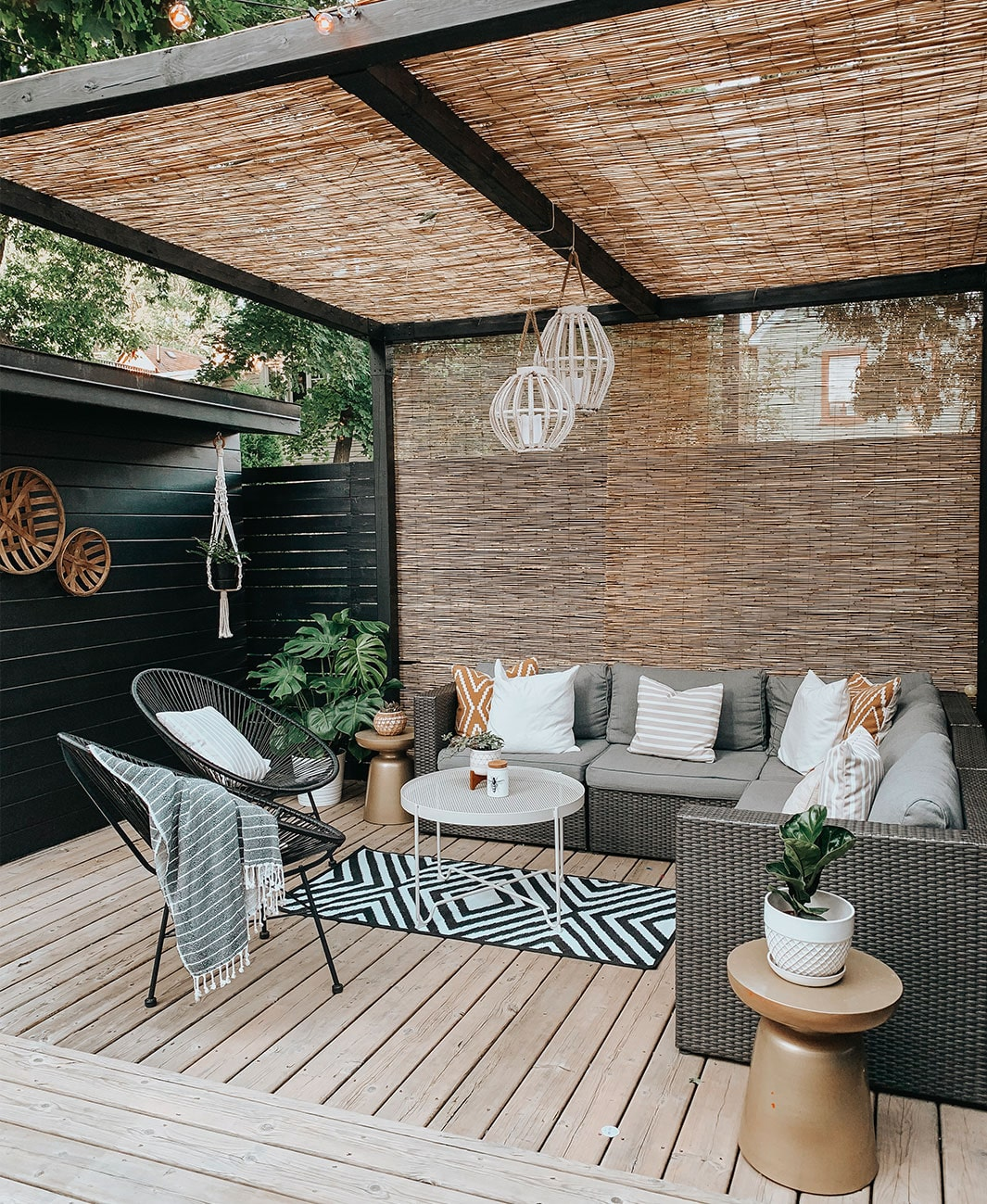 A stylish backyard deck with an outdoor couch and two chairs, a print rug, a white coffee table and a plant on a side table.
