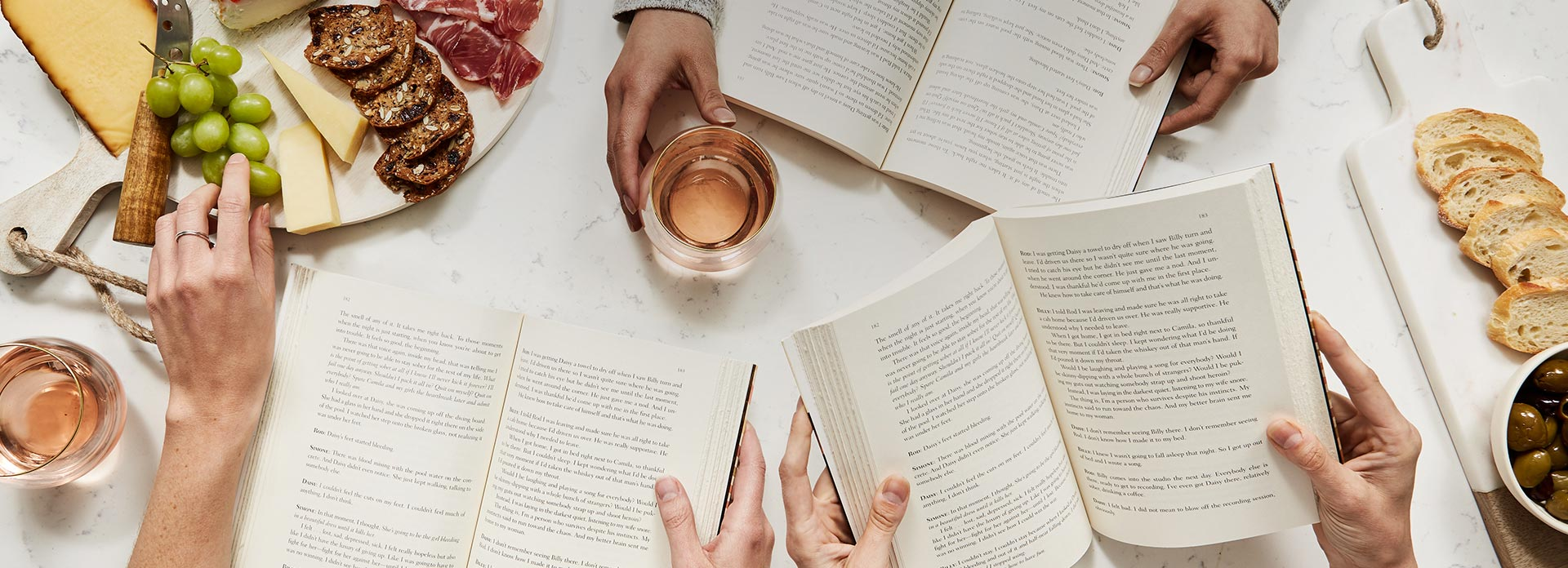 Aerial shot of three sets of hands with open books, and a glass of wine and a cheese board on a white marble table.