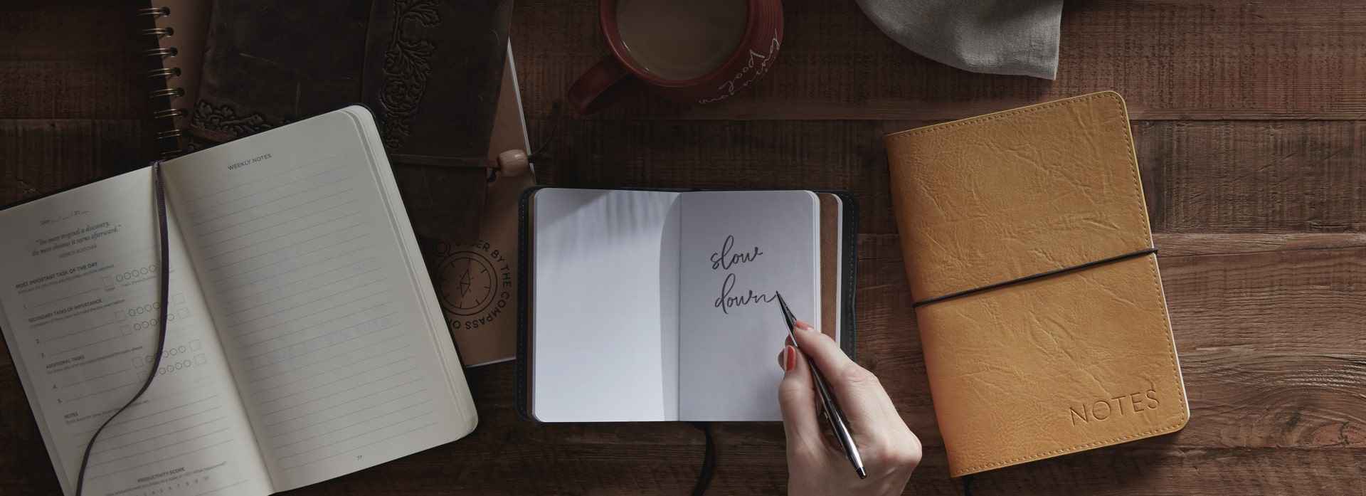 "Open book with a hand writing the words ""slow down"" beside an mug filled with coffee"