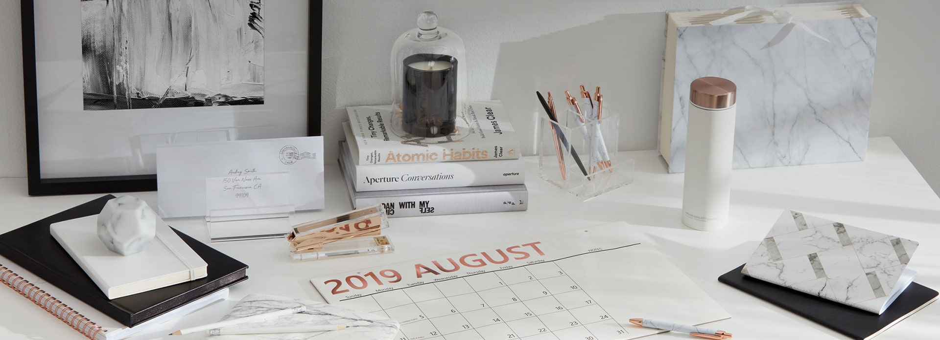 Monochrome desk with books stacked, calendar, pen holder, pencil, and marble pencil case