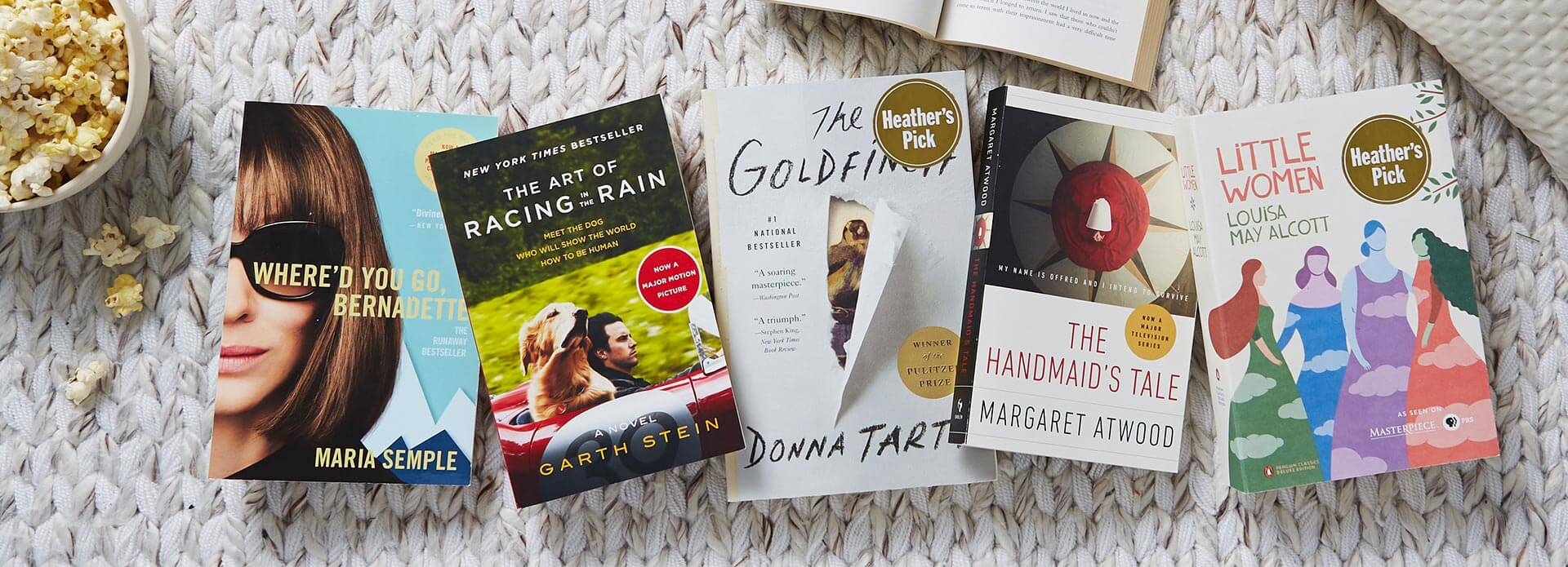 A flat lay of books on a white rug, including Where'd You Go, Bernadette, Little Women, The Handmaid's Tale, The Goldfinch, and The Art of Racing in the Rain.