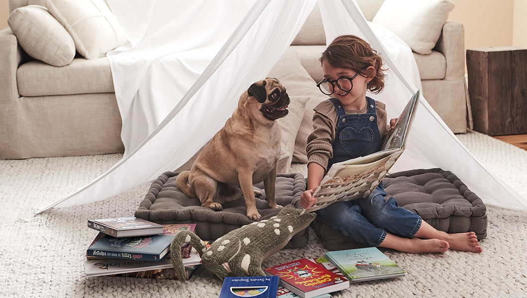 Little girl sitting with her pug dog surrounded by picture books and reading a large picture book