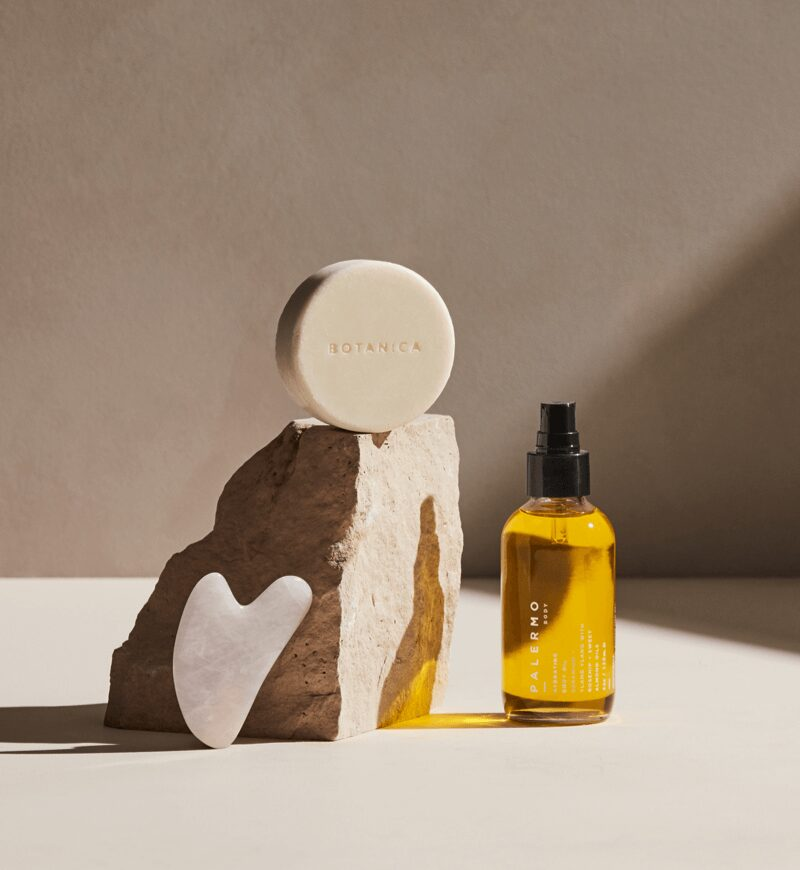 New wellness products featuring a rose quartz facial gua sha, a bottle of Palermo Body body oil and Botanica soap.