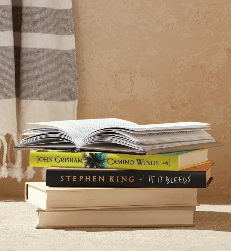 A stack of books featuring Camino Winds by John Grisham.