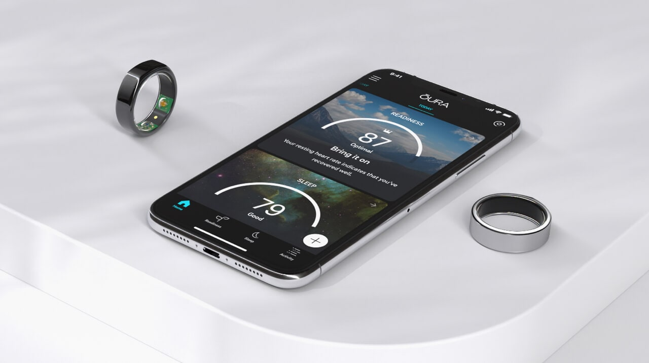 A table with a couple of Oura rings and a mobile phone displaying the Oura app.