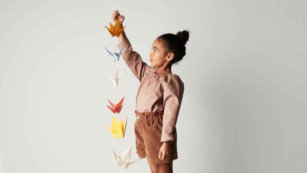 A child holding a chain of paper cranes in one hand.