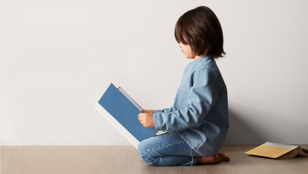 A child sitting on the floor reading a book.