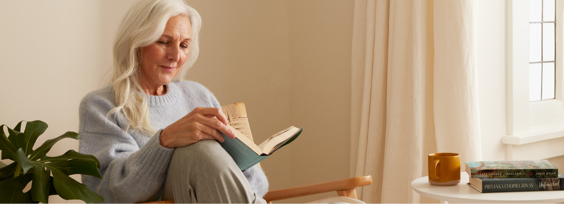 A woman sitting on a chair reading a book.