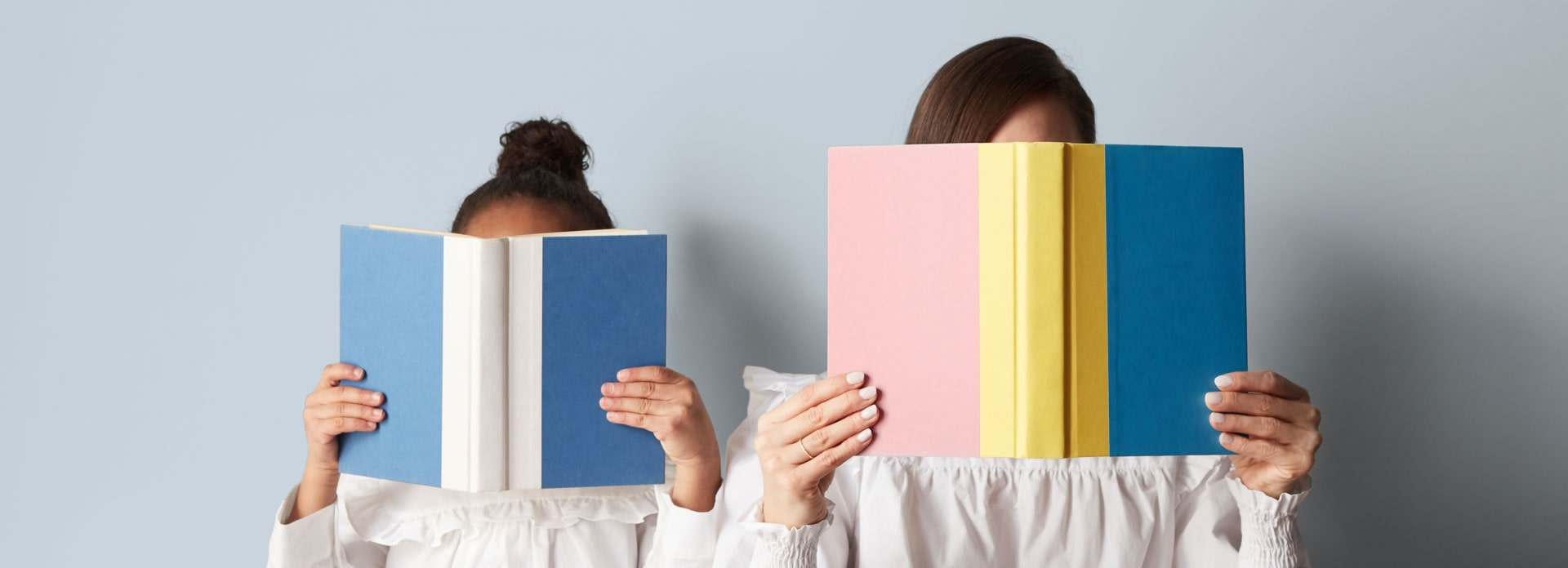 A pair of people holding up books covering their faces.