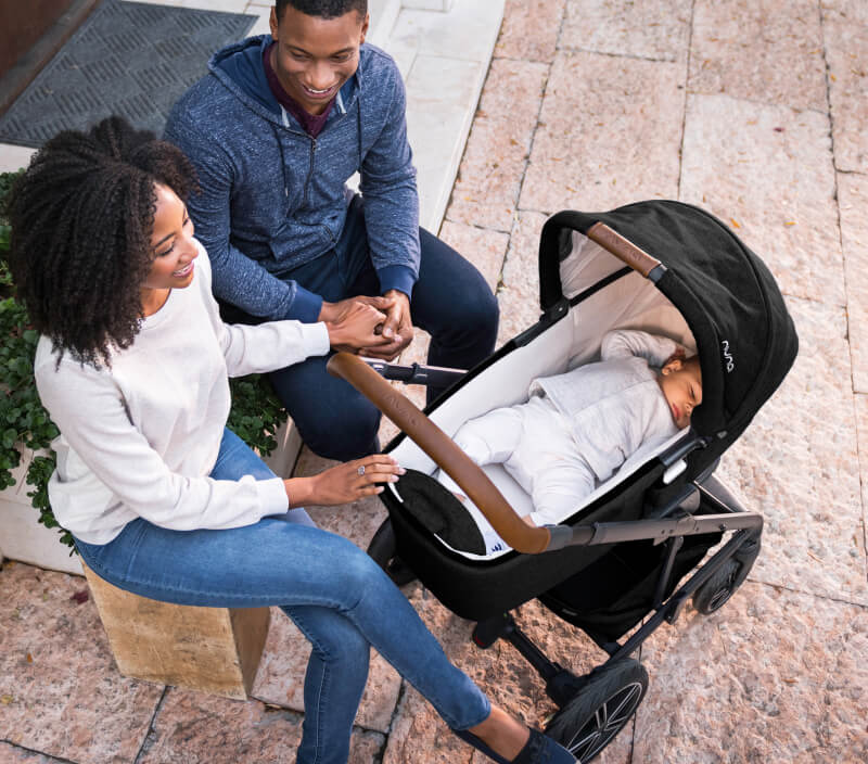 A couple seated on an outdoor bench watching over a sleeping baby lying in a baby stroller.