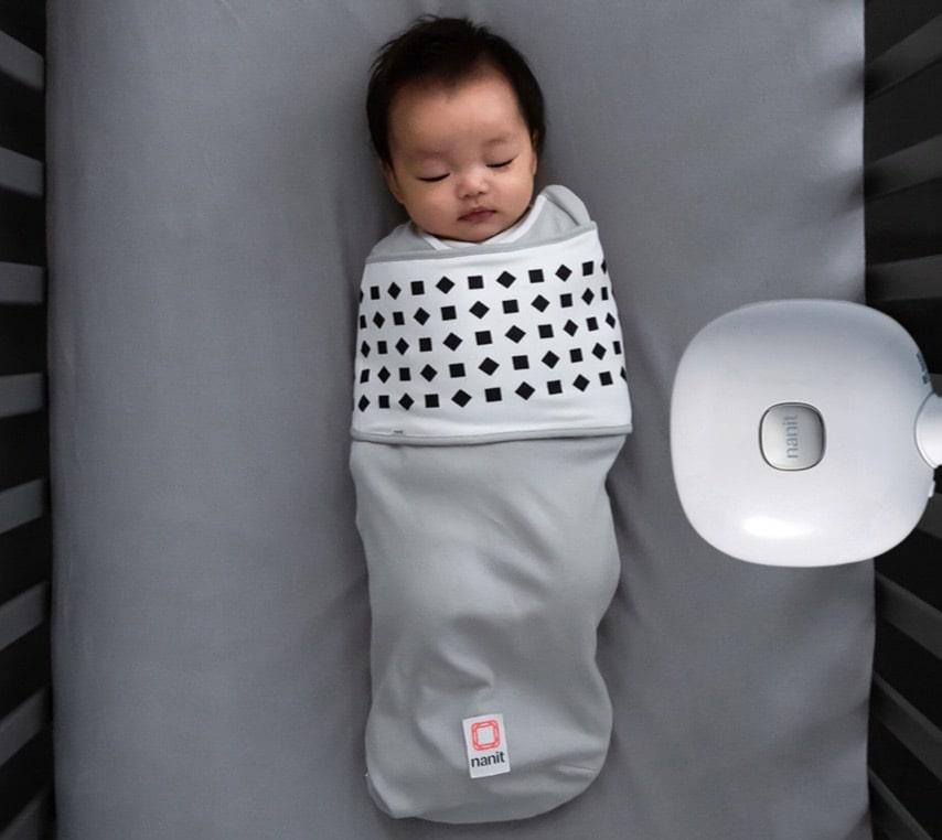 A bird's eyeview of the Nanit Breathing Wear Baby Monitor overloooking a sleeping baby in a crib.