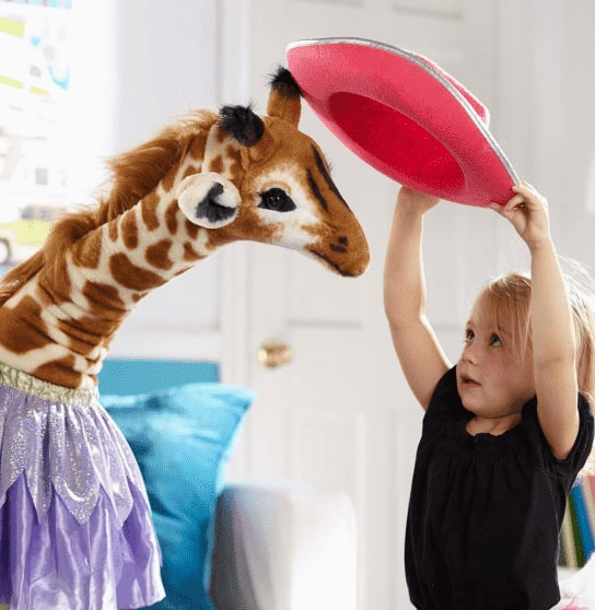 A little girl holding a hat up over her head and setting it on a stuffed giraffe.