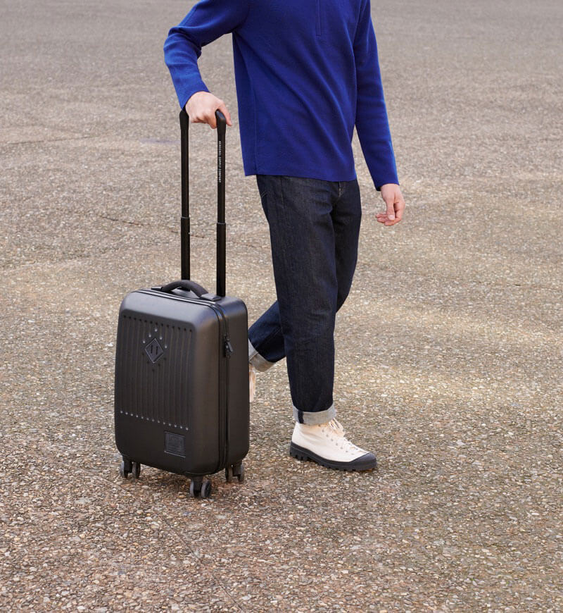 A person walking on pavement holding the handle of a Herschel Supply Co. black hard shell suitcase.
