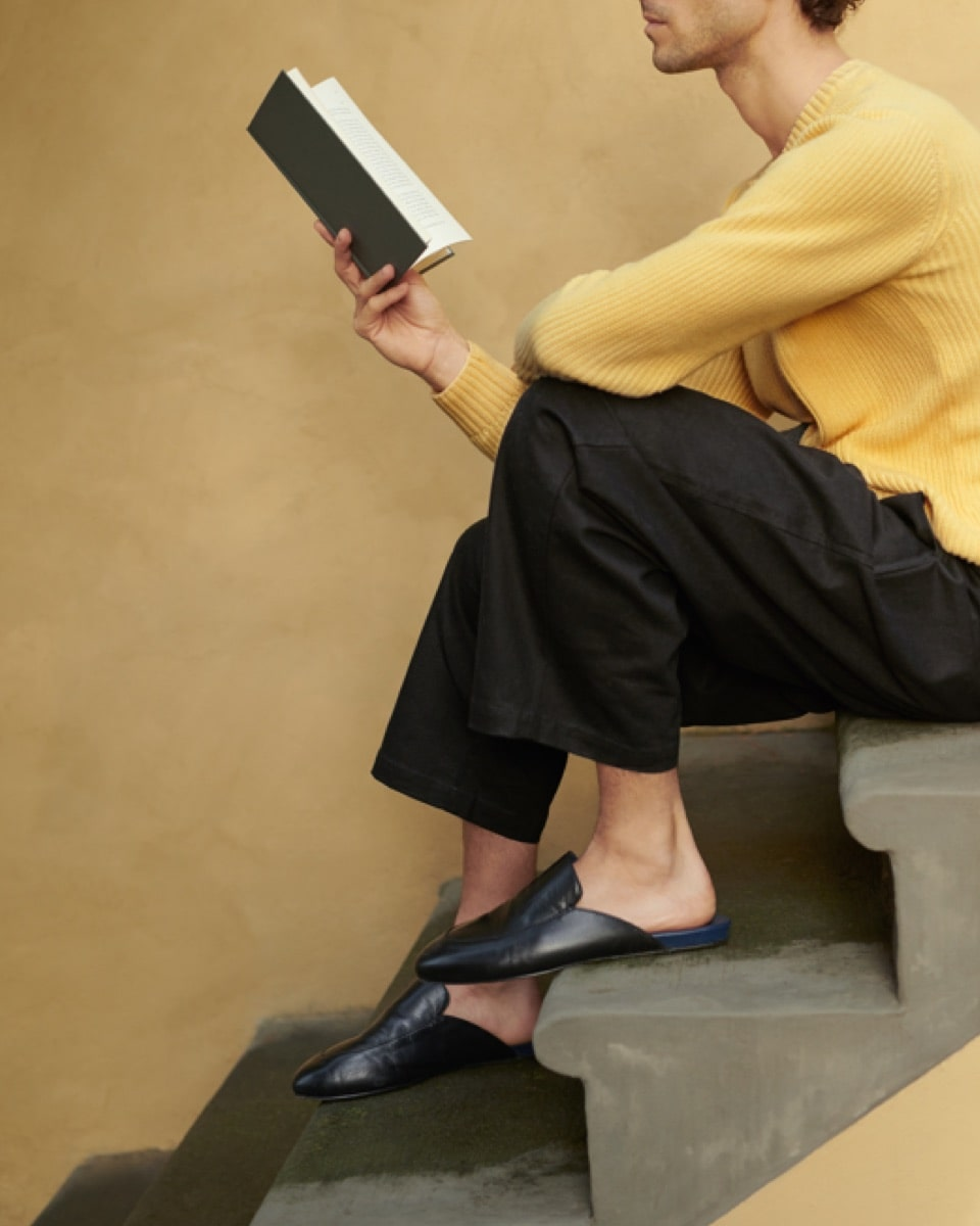 A person sitting on the stairs reading a paperback book.