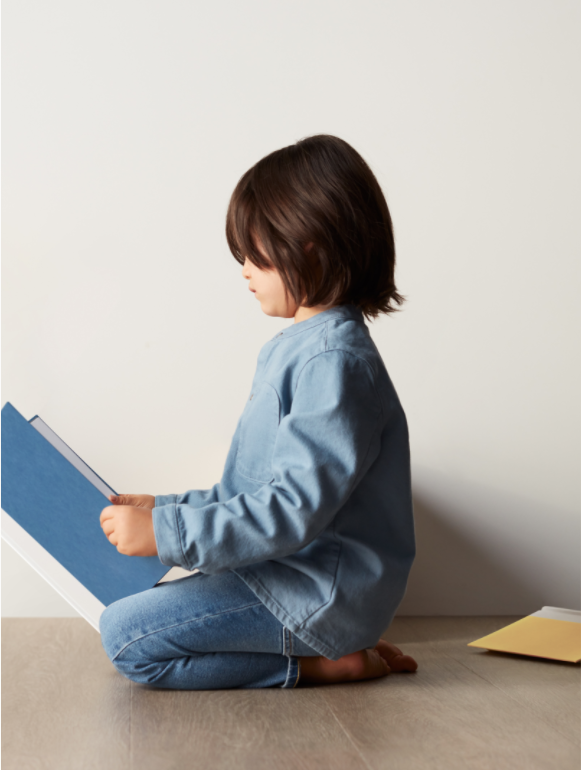 A child sitting on the floor reading a book