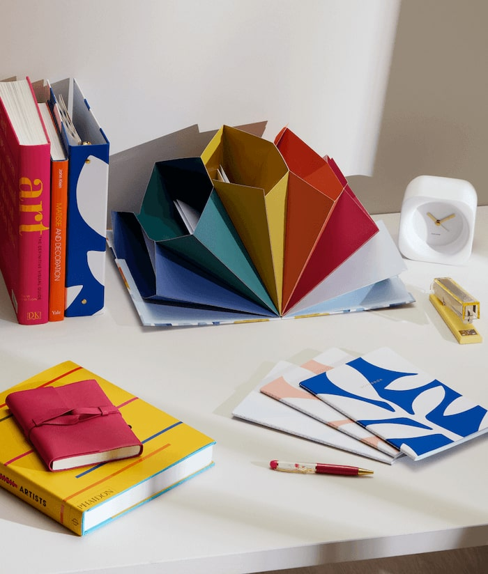 A desk with colourful notebooks and file organizers.