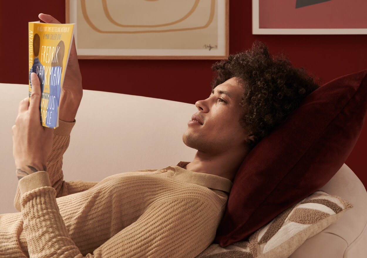 A person lying on the couch reading a book.
