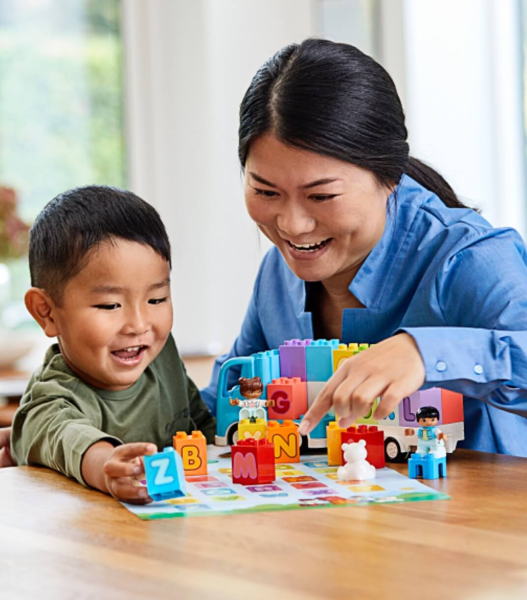 A parent with their child playing with LEGO interlocking blocks.