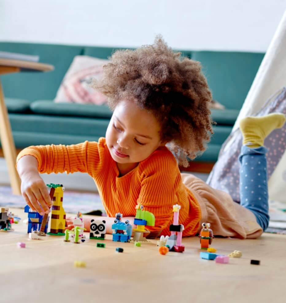 A child playing with LEGO on the floor.