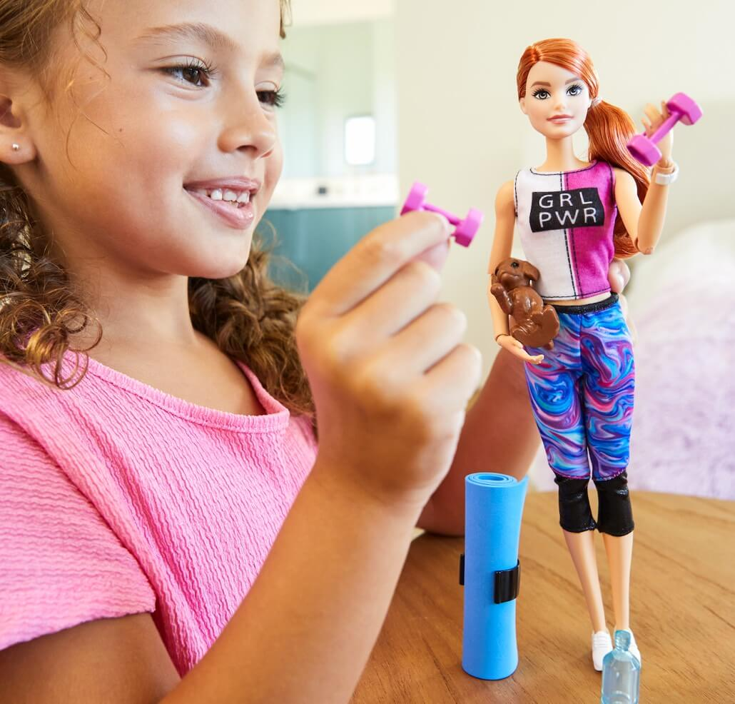 A girl playing with a barbie wearing workout clothes.