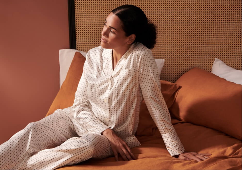 A person wearing silk loungewear sitting on a bed.