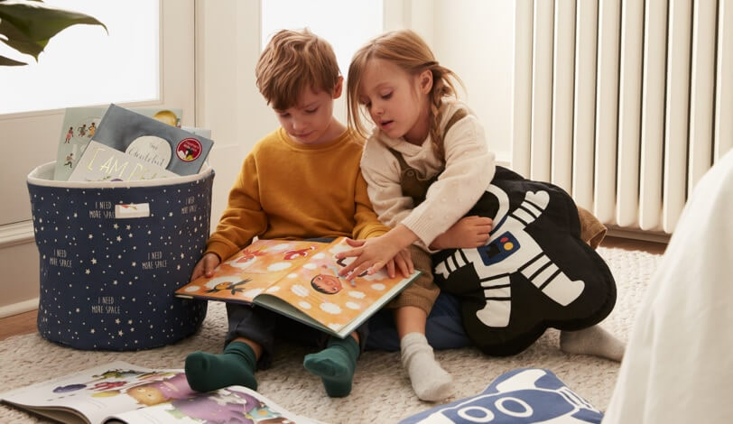 Two children reading a children's book together.