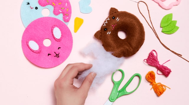 Someone crafting felt donuts.