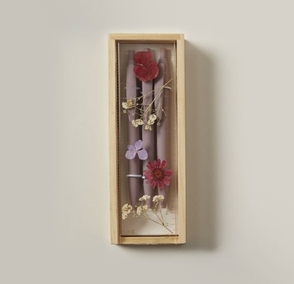 A wooden pencil case with a ruler embedded with real dried flowers placed on top.