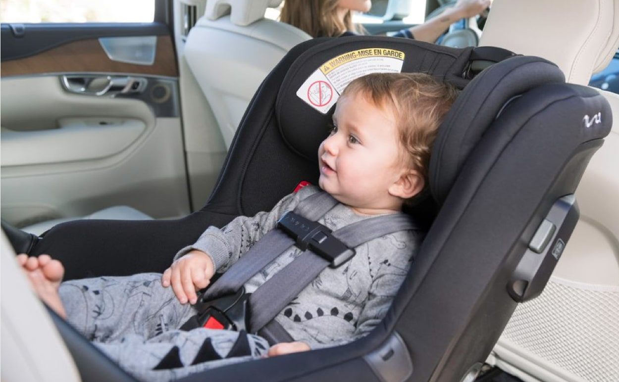 A baby sitting in a rear-facing car seat.