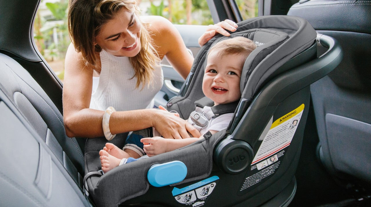A mother securing her baby into a rear-facing car seat.