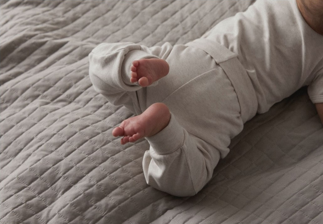 A crawling baby wearing the littlest clothes.