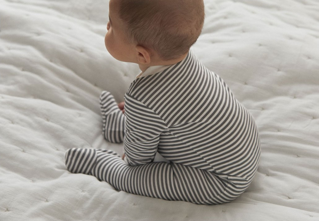 A baby wearing a striped onesie by the littlest.