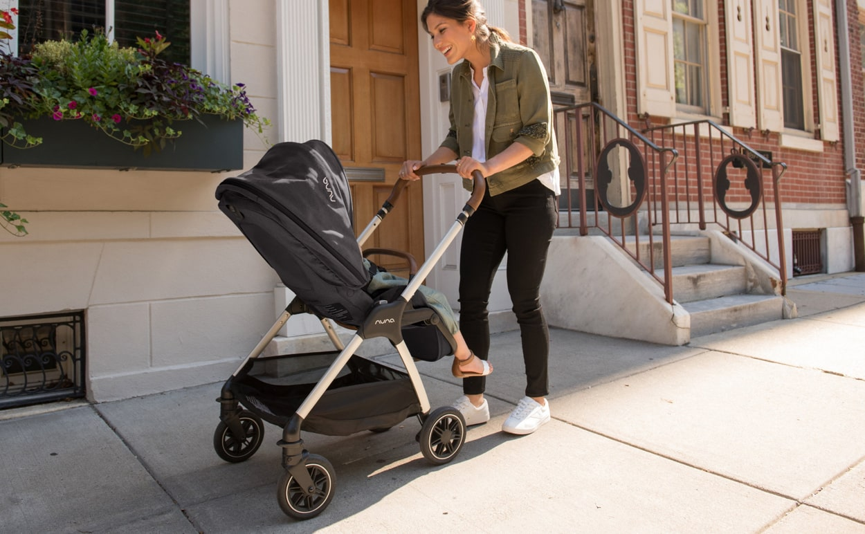 A mother walking down a sidewalk while pushing a baby stroller.