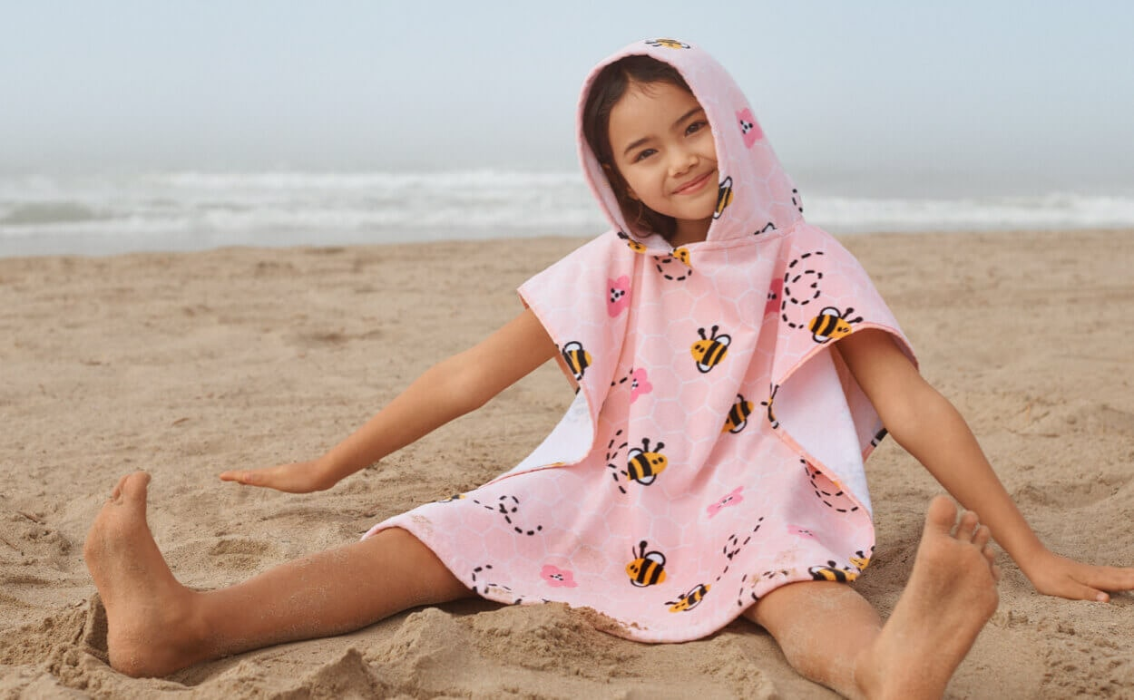 A child wearing a bumble bee poncho towel from the Summer Essentials Collection by Wonder Co.