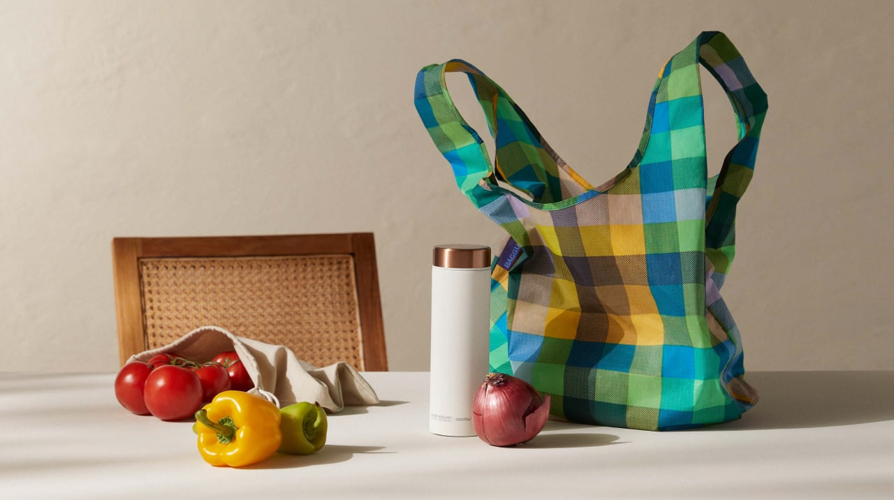 A reusable water bottle and reusable shopping bags filled with fruit.