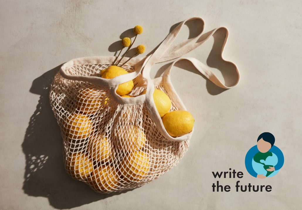 A reusable mesh tote filled with oranges